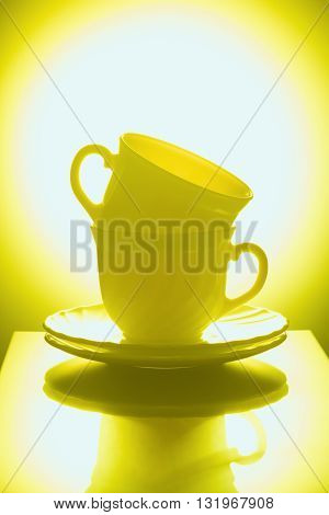 Cups for tea with saucers on a yellow background