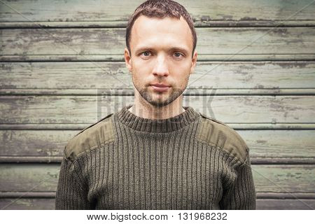 Young Caucasian Man In Military Green Sweater