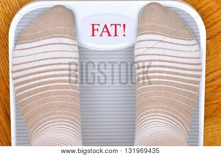 Person standing on the weight scale. The scale shows FAT!