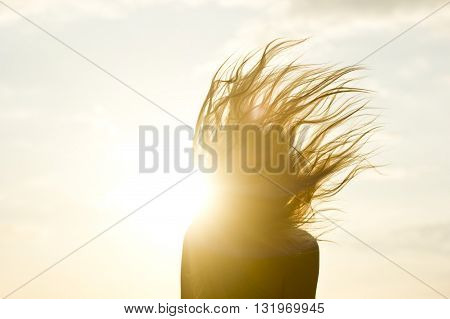 silhouette of girl's hair up against the yellow sun rays
