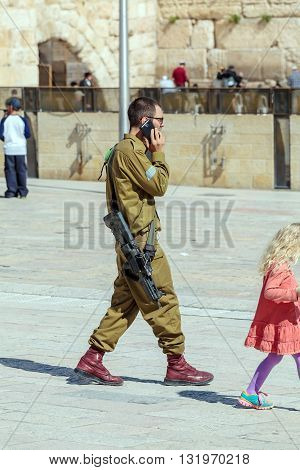 Jerusalem, Israel - February 17, 2013: Armed Young Soldier Speaking Mobile Phone Near Western Wall
