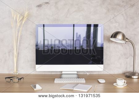 Creative desktop with city reflection on computer monitor wheat spikes glasses smart phone notepad coffee cup and lamp on concrete background