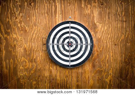 Empty dartboard on wooden background, free space