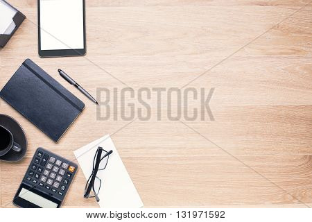 Wooden desk with office tools on its left side. Topview Mock up