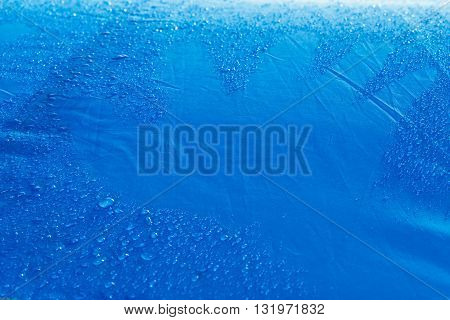 Rain Water droplets on blue fiber waterproof fabric with Hand trace on fabric