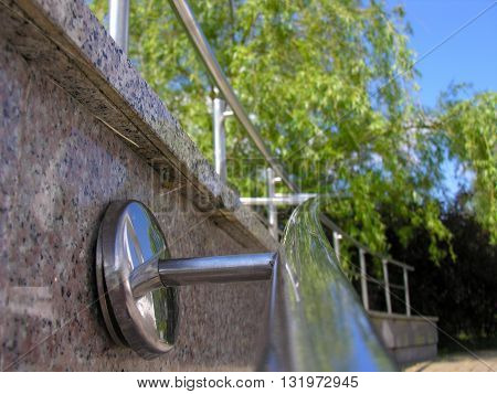 Trees and sky reflected in a steel handrail marble stairs in the park
