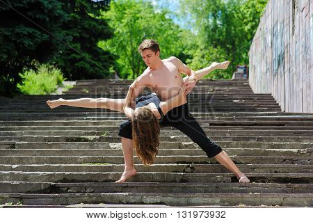 Contemporary dance. Man and woman in passionate dance pose in park. Young couple dancing modern dance. Girl doing splits. Man with naked torso. Old stairs in park, trees in background.