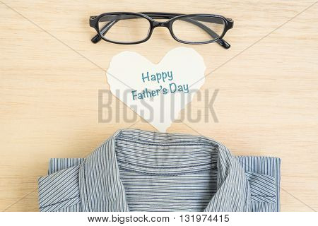 Happy Father's Day - Top view of Happy Father's Day on heart shape paper with black glasses and half blue shirt on wooden background