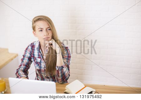 Attractive caucasian girl sitting in office at wooden desk with laptop orange juice and laptop on white brick wall background