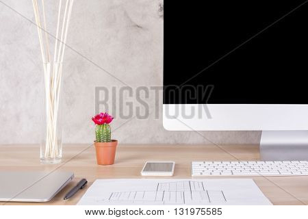 Creative desktop with blank computer monitor cactus smart phone closed laptop construction drawing and other items on concrete wall background. Mock up