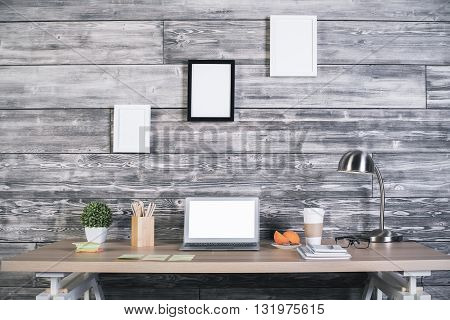 Front view of modern designer workplace with blank white laptop coffee lamp various stationery items and three blank picture frames hanging above on wooden wall. Mock up