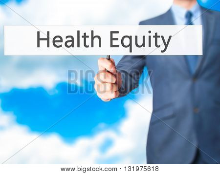 Health Equity - Businessman Hand Holding Sign