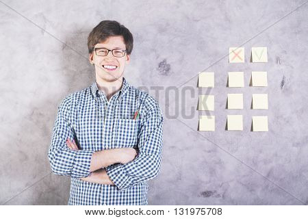 Smiling caucasian man with green and pencils in shirt pocket standing next to concrete wall with cross and tick on stickers