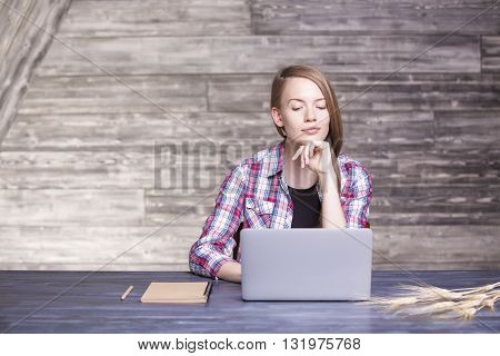 Thoughtful young woman looking at laptop screen placed on wooden desktop with notepad and wheat spikes