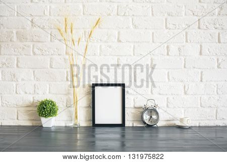 Blank picture frame alarm clock plant wheat spikes and coffee cup on wooden desktop and white brick wall background. Mock
