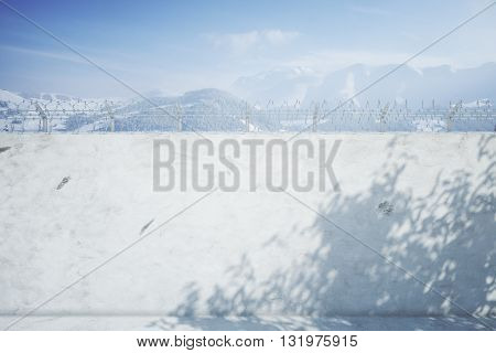 Concrete prison wall with shadows and snowy mountains view. Mock up 3D Rendering