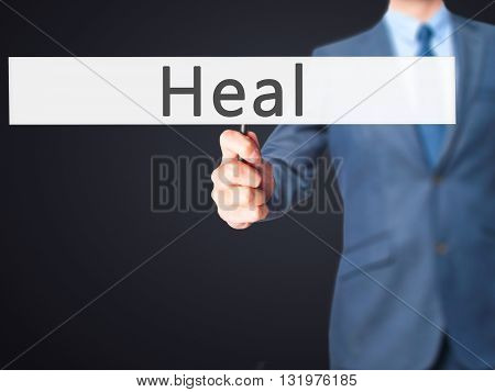 Heal - Businessman Hand Holding Sign