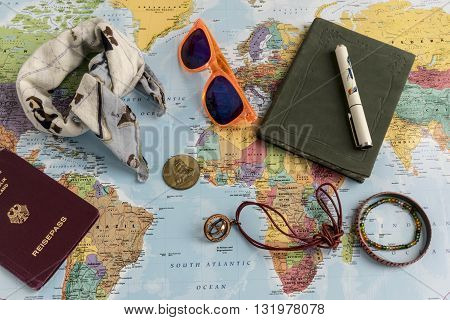 World travel concept with bandanna tinted glasses coins talisman journal and passport objects on top of map