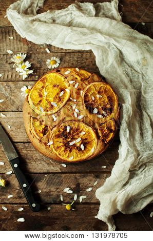 Delicious fresh homemade pie with orange zest milk butter eggs. Decorated with slices of orange on a wooden background. Cake sprinkled with powdered sugar. Decorated with wild flowers