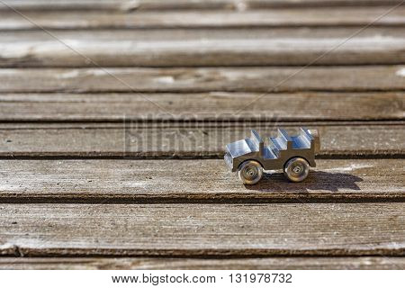 Close up on tiny die cast metal toy open top car on sunny wooden deck with copy space