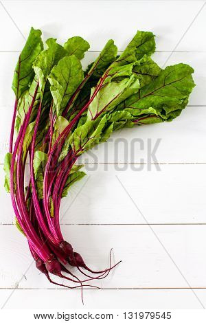 Beet leaves on white wooden table flat lay.