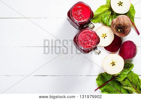 Red smoothies from beetroot beet leaves and apple on white wooden table with copy space. Flat lay.