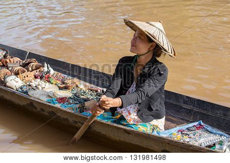 INLE LAKE MYANMAR - JANUARY 14 2016 : Unidentified Burmese woman on small long wooden boat selling souvenirs trinkets and bijouterieat the floating market on Inle Lake Myanmar