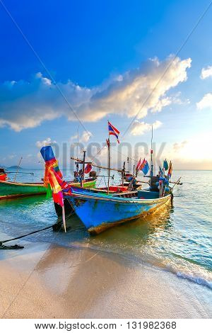 Colorful fishing boats of wood on the coast of a sandy beach. Thailand