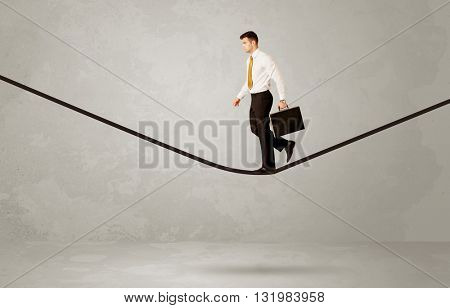 An elegan businessman in suit balancing on a tight rope with a briefcase in front of grey urban wall background environment concept