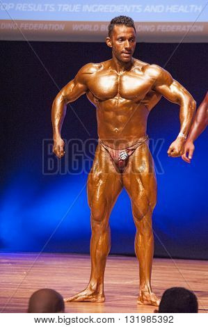 MAASTRICHT THE NETHERLANDS - OCTOBER 25 2015: Male bodybuilder flexes his muscles and shows his best physique in a front pose on stage at the World Grandprix Bodybuilding and Fitness of the WBBF-WFF