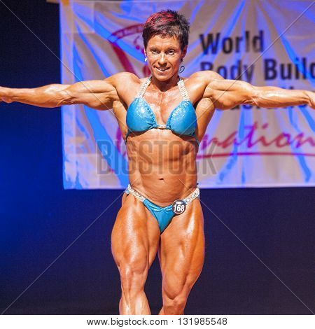 MAASTRICHT THE NETHERLANDS - OCTOBER 25 2015: Female bodybuilder Michèle Steenhaut shows her best pose of her individual routine at championship on stage at the World Grandprix Bodybuilding and Fitness