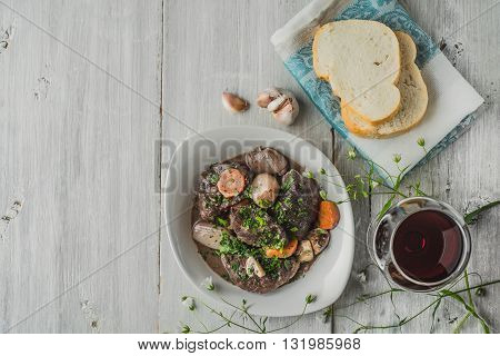 Beef bourguignon in a white ceramic plate with flowers and glass of wine horizontal
