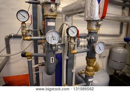 Close up of pipes valves and manometer of heating system