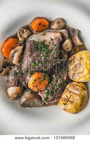 Beef bourguignon in a ceramic plate with grilled potatoes vertical