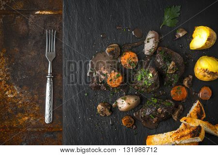 Beef bourguignon on the black stone grilled potatoes and fork horizontal