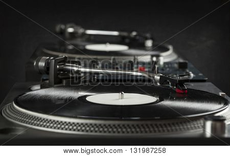 Turntable playing vinyl close up with needle on the record with grey background