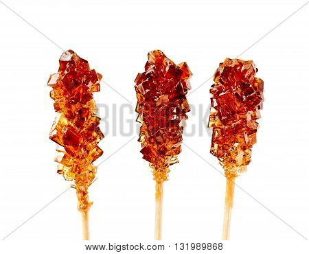 Close up of three brown sugar stirrers isolated on white.