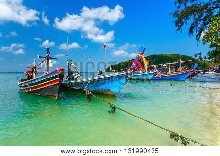 Wooden fishing boat near the sandy sea shore in the turquoise waters.