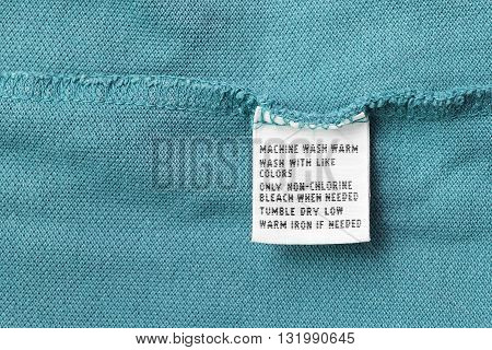 Washing instructions clothes label on blue cloth as a background