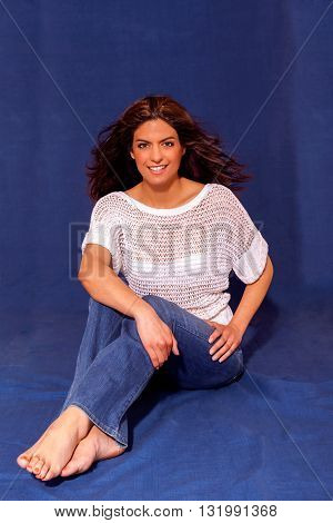 Laughing young woman relaxing and sitting against a wall