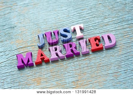 Just Married Phrase On Vintage Wooden Background