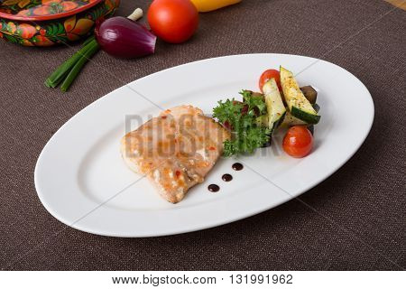 Salmon steak with grilled vegetables on a white plate
