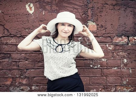 Pretty young woman in white blouse and hat posing against brick wall background. Woman holds the edges of the hat by hands. Toned photo with copy space. Vintage style photo.