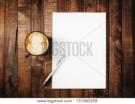 Blank branding template on vintage wooden table background. Letterhead coffee cup and pen. Blank stationery. Mock-up for branding identity for design portfolios. Top view.