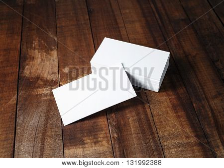 Blank white business cards on vintage wooden table background. Template for branding identity.