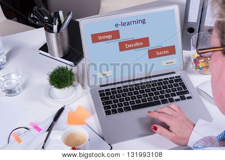 woman is e-learning with computer having a coffee