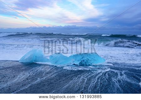 Blue icebergs at black beach in south Iceland