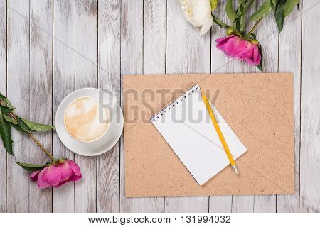 Notebook with a pencil next to coffee and peonies flowers on the wooden background. Top view.