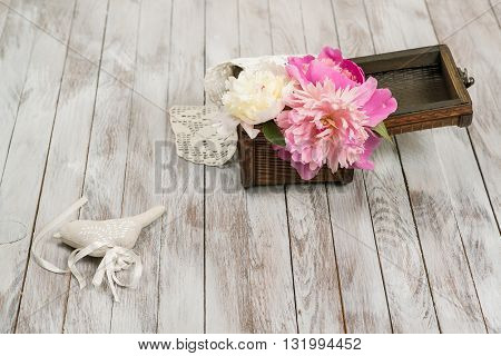 Beautiful flowers peonies in basket and decoration on the light wooden background.