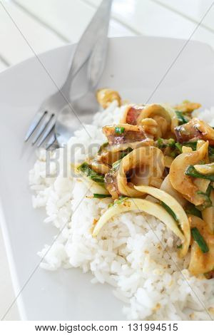 rice and squid with curry powder in white dish on wood table